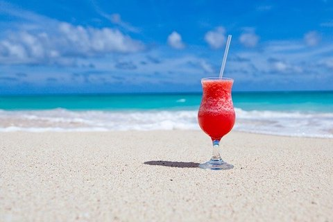 Röd drink på en strand